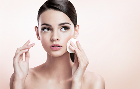 removing: Beautiful brunette lady removing makeup from her face, skin care concept