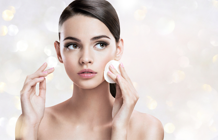 glowing skin: Beautiful brunette woman removing makeup from her face, skin care concept Stock Photo