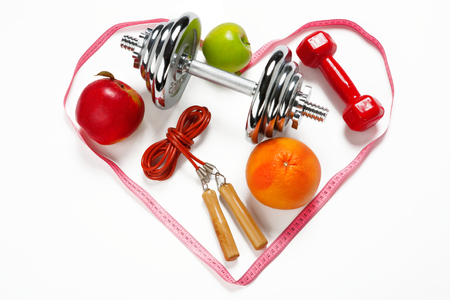 Sporty still life. Heart shape arrangement - photo of weight training and fitness equipment on white background photo