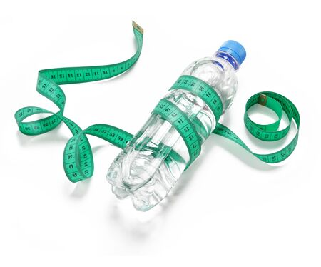 fat burning: Plastic bottle with water and measuring tape