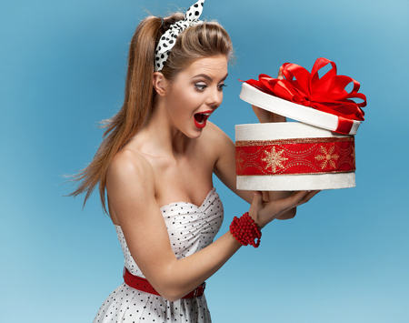 pin up vintage: Eccitato ragazza di compleanno di apertura regalo a sorpresa con uno sguardo di stupore e shock Archivio Fotografico