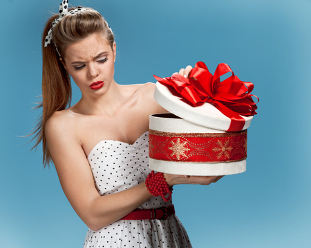 hair wrapped up: Suspicious girl opening gift box Stock Photo