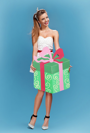 hair wrapped up: Sexy retro pin-up girl holding green gift box with a bow