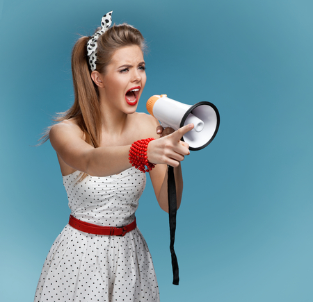 speaking trumpet: Pin-up girl holding a mouthpiece, speaking trumpet. Filmmaking or film production concept Stock Photo