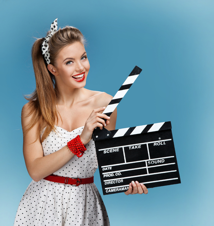clap: pin-up girl holding a Clapper board. Filmmaking or film production concept Stock Photo