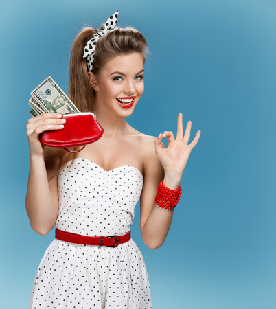 Thrilled young lady holding cash and happy smiling. Shopping concept Imagens