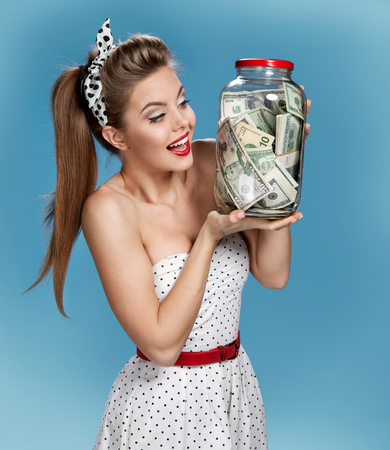 pinup: Retro woman with a jar of money having an idea How to Spend Money. Shopping concept Stock Photo
