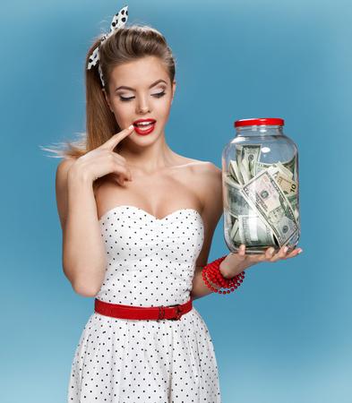 pin up vintage: Retro donna con un vasetto di denaro che ha un'idea come spendere i soldi. Shopping concetto