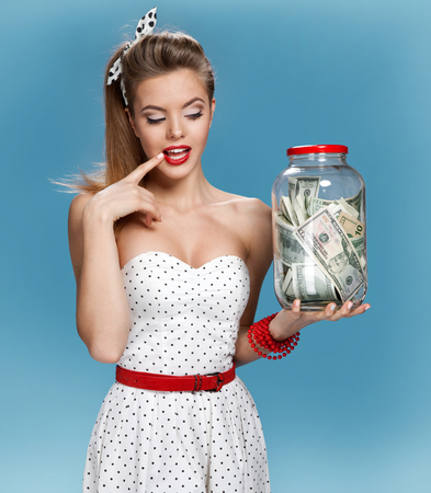 pin up: Retro woman with a jar of money having an idea How to Spend Money. Shopping concept Stock Photo