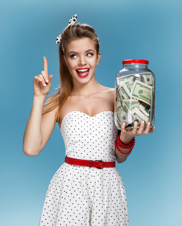 Retro woman with a jar of money having an idea How to Spend Money. Shopping concept Foto de archivo