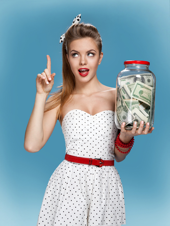 happy rich woman: Pin-up girl with a jar of money having an idea how to spend them. Shopping concept