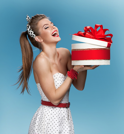 make a gift: Surprised laughing beautiful young woman holding an open gift box over blue background. Holidays, holiday, celebration, birthday and happiness concept