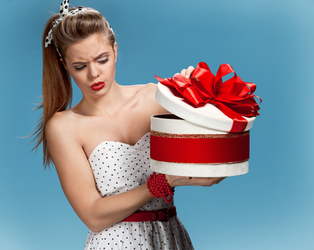 makeups: Thoughtful girl holding holiday or birthday presents, gift box on blue background. Holidays, celebration, birthday concept