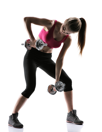 pull up: sporty muscular female brunette girl wearing sports clothes working out with dumbbells over white background