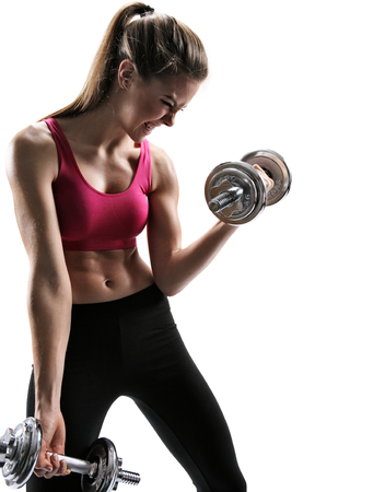 sporty muscular female brunette girl wearing sports clothes working out with dumbbells over white background