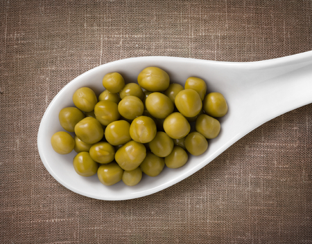 sackcloth: Canned peas in white porcelain spoon  high-res photo of grain in white porcelain spoon on burlap sackcloth background