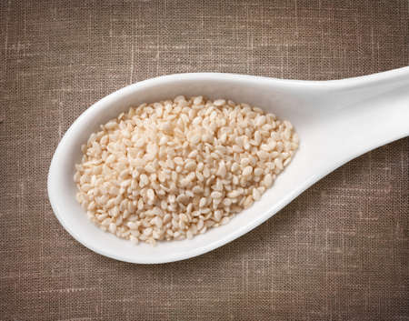 white sesame seeds: White sesame seeds in a wooden spoon  high-res photo of grain in white porcelain spoon on burlap sackcloth background