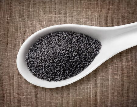sackcloth: Poppy seeds in a wooden spoon  high-res photo of grain in white porcelain spoon on burlap sackcloth background