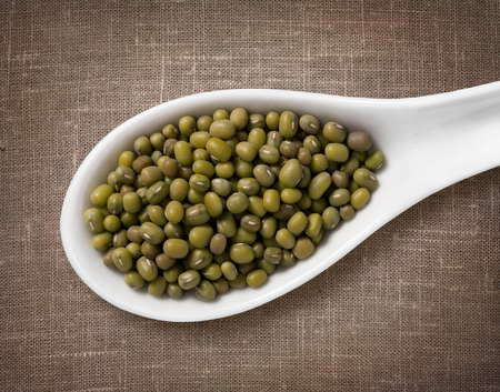 Mung beans in a wooden spoon  high-res photo of grain in white porcelain spoon on burlap sackcloth background photo