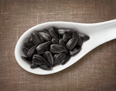 sackcloth: Black sunflower seeds in white porcelain spoon  high-res photo of grain in white porcelain spoon on burlap sackcloth background