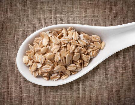 avena en hojuelas: Escamas Copos de avena en blanco cuchara de porcelana  foto de alta resoluci�n del grano en blanco cuchara de porcelana en el fondo de saco de arpillera