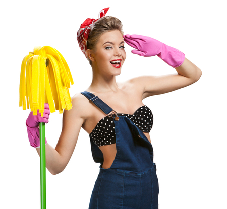 Beautiful woman wearing pink rubber protective gloves holding cleaning mop / young beautiful American pin-up girl isolated on white background. Cleaning service concept