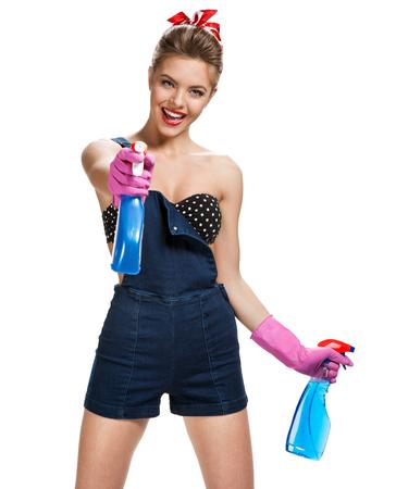 pin up vintage: Bella cameriera di indossare guanti protettivi di gomma rosa in possesso di bombolette spray per la pulizia  giovane bella ragazza americana pin-up isolato su sfondo bianco. Concetto di servizio di pulizia
