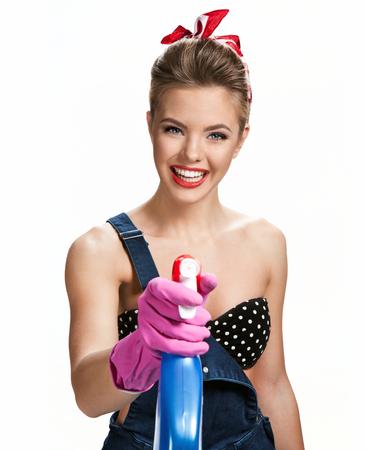 pulizia viso: Bella pulizia ragazza che indossa guanti protettivi di gomma rosa in possesso di spruzzo  giovane bella ragazza americana pin-up isolato su sfondo bianco. Concetto di servizio di pulizia