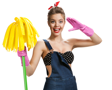 Beautiful pin-up girl wearing pink rubber protective gloves holding cleaning mop  young beautiful American pin-up girl isolated on white background. Cleaning service concept Zdjęcie Seryjne