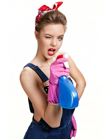 scour: Beautiful cleaning girl wearing pink rubber protective gloves holding spray  young beautiful American pin-up girl isolated on white background. Cleaning service concept