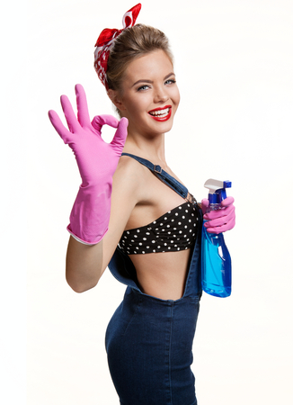 appealing: Appealing cleaning woman wearing pink rubber protective gloves holding spray Showing Us It Stock Photo