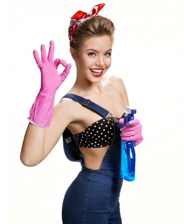 Sexy cleaning girl wearing pink rubber protective gloves holding spray Showing Us It