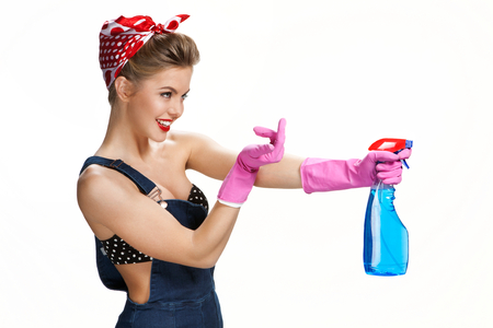 housewife gloves: Inviting housewife wearing pink rubber protective gloves holding spray  young beautiful American pin-up girl isolated on white background. Cleaning service concept
