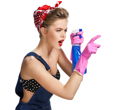 spray bottle: Thinking cleaning woman wearing pink rubber protective gloves holding spray bottle  young beautiful American pin-up girl isolated on white background. Cleaning service concept