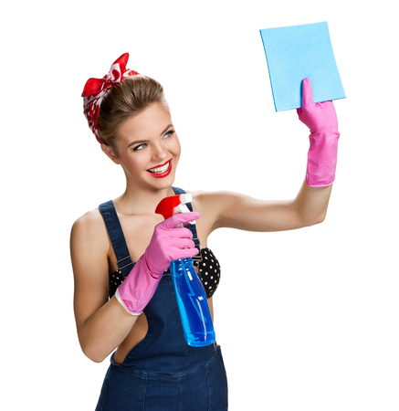 spray bottle: Beautiful staff wearing pink rubber protective gloves holding cleaning spray bottle and cellulose sponge  young beautiful American pin-up girl isolated on white background. Cleaning service concept