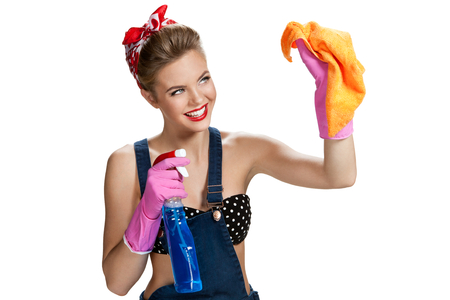 pulizia viso: Bella lavoratore indossare guanti protettivi di gomma rosa in possesso di panno per la pulizia flacone spray e arancio microfibra  giovane bella ragazza americana pin-up isolato su sfondo bianco. Concetto di servizio di pulizia