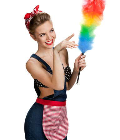 Young beautiful cleaning woman holding static duster and pointing to the right  young beautiful American pin-up girl isolated on white background. Cleaning service concept