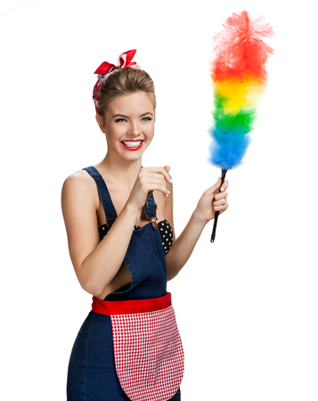 Young beautiful cleaning maid holding colorful static duster and smiling  young beautiful American pin-up girl isolated on white background. Cleaning service concept