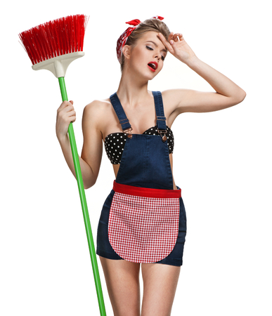 Tired maid standing after spring cleaning with broom  young beautiful American pin-up girl isolated on white background. Cleaning service concept Stock Photo