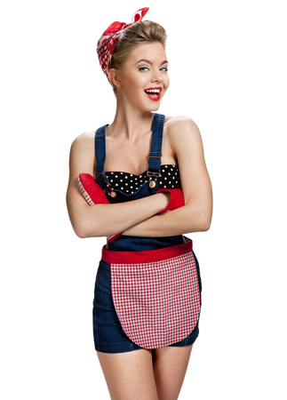 apron: Obstinate maid wearing apron with arms across  young beautiful American pin-up girl isolated on white background. Cleaning service concept Stock Photo