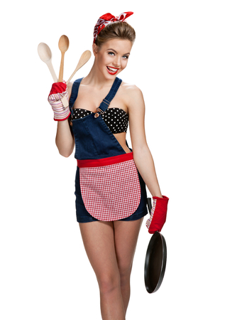 Appealing maid wearing apron with kitchen utensils  young beautiful American pin-up girl isolated on white background. Cleaning service concept photo