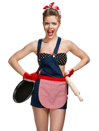 pin up: Angry housewife with battledore and black frying pan  young beautiful American pin-up girl isolated on white background. Cleaning service concept