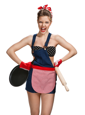 contentious: Quarrelsome maid wearing apron with wooden rolling pin and black frying pan  young beautiful American pin-up girl isolated on white background. Cleaning service concept