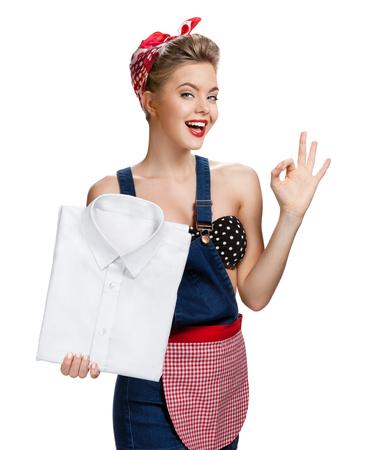pin up vintage: Donna felice che tiene la camicia bianca di bucato e ci mostra che