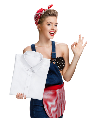 up service: Happy woman holding laundered white shirt and showing us it Stock Photo