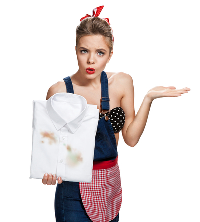 make dirty: Disappointed wife holding dirty white shirt and showing incomprehension