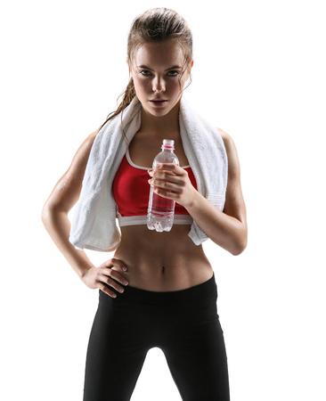 흰색 배경 위에 스포츠 옷을 입고 스포티 한 근육 여성 갈색 머리 여자의 물 사진 세트의 수건 병 아름 다운 소녀 스톡 콘텐츠