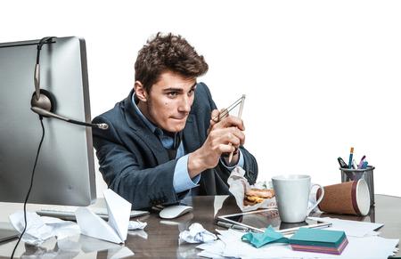 Geconcentreerde man met katapult doel modern kantoor man op werkende plaats luiheid en gemakzucht begrip