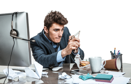 Concentrated man with slingshot aim  modern office man at working place sloth and laziness concept