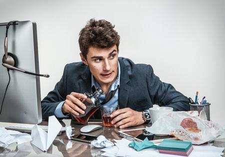 アルコール中毒問題概念で意気消沈した身に着けている緩いネクタイを探してガラスを保持しているコンピューターのオフィスで座って酔って酔っ